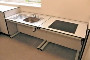 Enhanced access food tech height adjustable tables with sink and electric hob