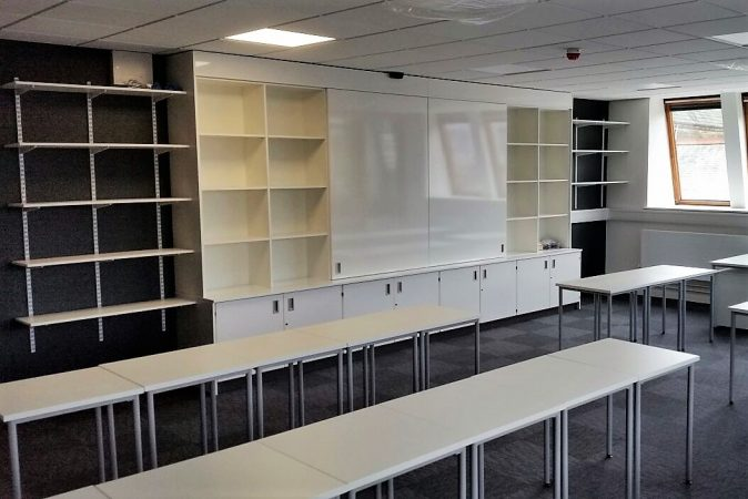 Teaching wall with sliding doors centred to reveal storage system